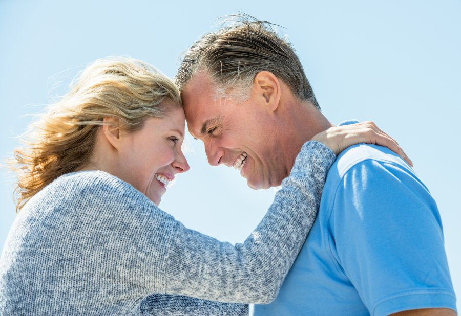 Side view of happy mature couple looking at each other against clear blue sky